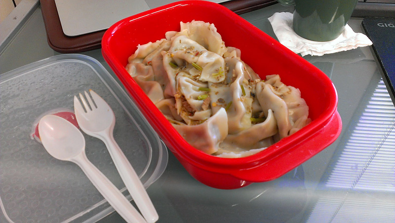 Boiled dumplings in a red lunch box, next day at work
